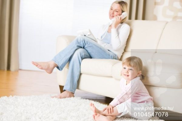 Mother and child in living room watch television, mother on phone in background on sofa, Kép: 104547078, License: Royalty-free, Megkötések , Model Release: yes, Kredit: Profimedia, CandyBox