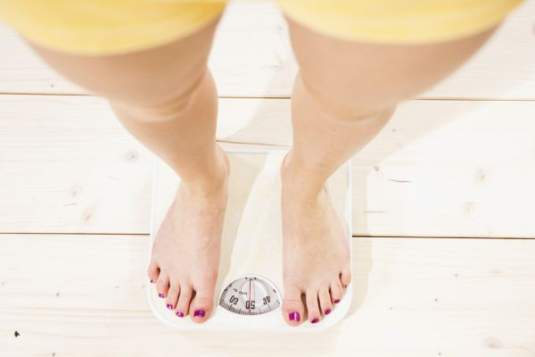 Young woman standing on a scale and checking her weight, Image: 151250330, License: Royalty-free, Restrictions: , Model Release: yes, Credit line: Profimedia, imageBROKER