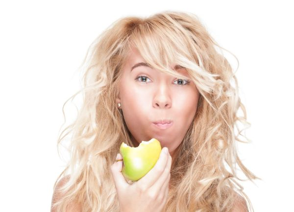 Beautiful woman chewing green apple. Young girl holding fresh fruit. Model isolated on white background. Motivation for diet and healthy lifestyle. Positive person with happy facial expression., Image: 143472623, License: Royalty-free, Restrictions: , Model Release: yes, Credit line: Profimedia, Alamy