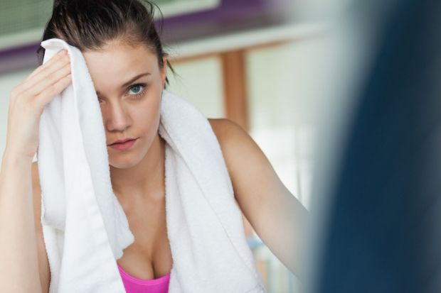 Tired young woman wiping face while working on row machine in fitness studio, Image: 177014443, License: Royalty-free, Restrictions: , Model Release: yes, Credit line: Profimedia, Wavebreak