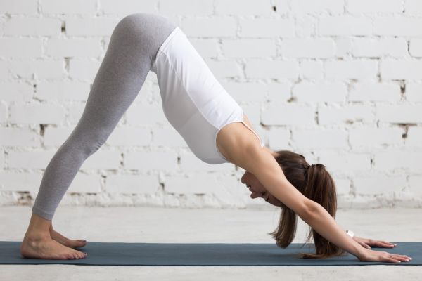 Beautiful young woman working out indoors, doing yoga exercise in the room with white walls, downward facing dog pose, adho mukha svanasana (sun salutation pose), full length, side view, Image: 277920735, License: Royalty-free, Restrictions: , Model Release: yes, Credit line: Profimedia, Alamy