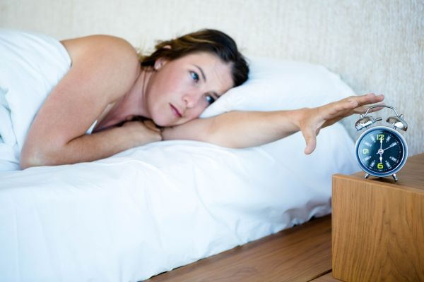 tired woman llying in bed reaching out to turn off her alarm, Image: 279994083, License: Royalty-free, Restrictions: , Model Release: yes, Credit line: Profimedia, Wavebreak