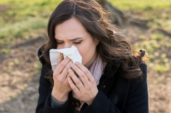 Portrait of young woman blowing her nose outdoor