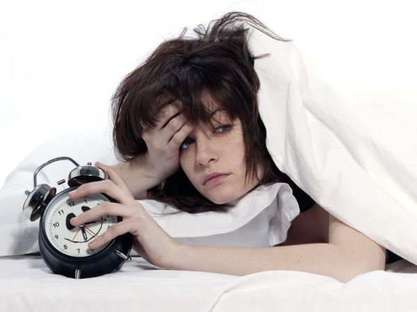 15091150 - young woman woman in bed awakening tired holding alarm clock on white background
