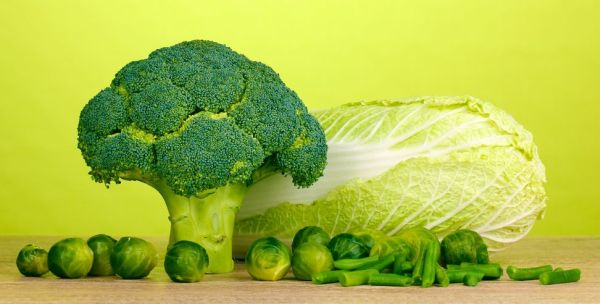 13688996 - fresh broccoli and cabbages on wooden table on green background
