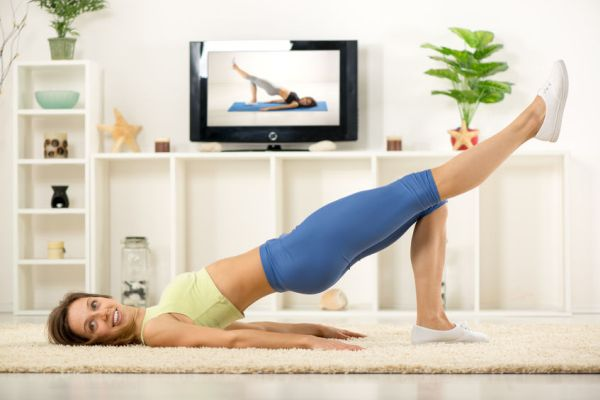 39762576 - young woman in sports clothes, doing exercises in the room, in front tv.