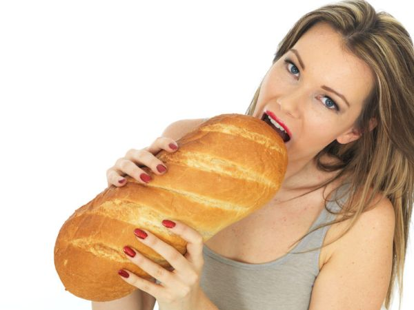 35230162 - attractive young woman holding a loaf of white bread