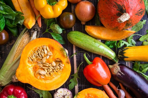 47701648 - fresh vegetables scattered on a old rustic dark textured table. autumn background. healthy eating. sliced pumpkin, zucchini, squash, bell peppers, carrots, onions, cut garlic, tomatoes, eggplant, corn cob, rucola and basil. top view