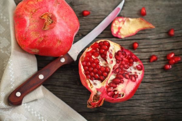 10759720 - juicy riped pomegranate  and knife on the wooden table