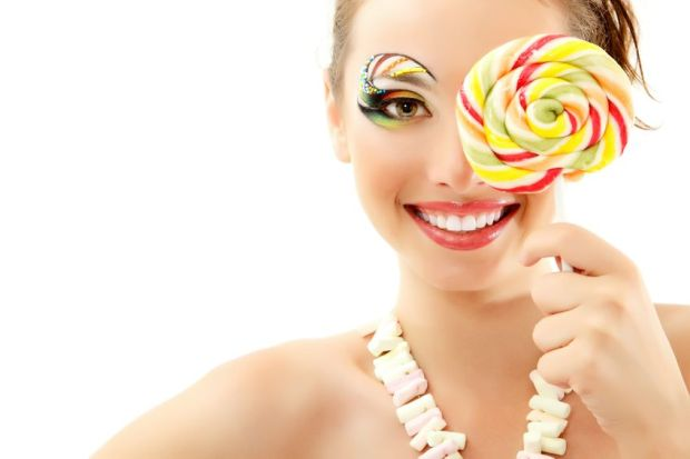 12106425 - woman laughing with candy and beautiful make-up young attractive isolated on white background