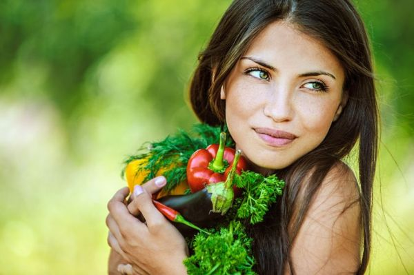 13636858 - portrait of young beautiful woman with bare shoulders holding a vegetable - parsley, pepper, eggplant, on green background summer nature.