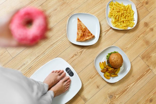 48712087 - diet and fast food concept. overweight woman standing on weighing scale holding donuts. french fries, hamburger and pizza. unhealthy junk food. dieting, lifestyle. weight loss. obesity. top view