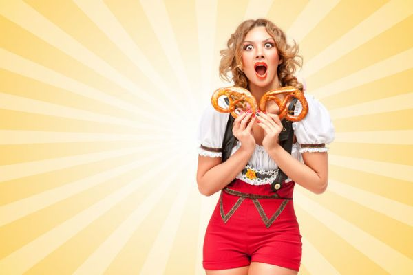 45415382 - beautiful sexy woman wearing red jumper shorts with suspenders in a form of a traditional dirndl, holding with hunger two pretzels on colorful abstract cartoon style background.