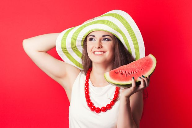 31266519 - beautiful young woman holding watermelon against red background