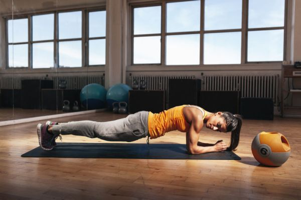 43852654 - young muscular woman doing core exercise on fitness mat in the gym. fit female doing press-ups during the training in the health club.