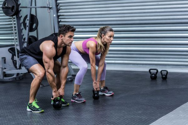 42329548 - squatting muscular couple lifting kettlebells at the crossfit gym
