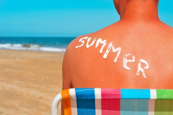 20165384 - the word summer written with sunblock on the sunburnt back of a man who is sunbathing on the beach