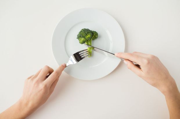 41728343 - healthy lifestyle, diet, vegetarian food and people concept - close up of woman with fork and knife eating broccoli