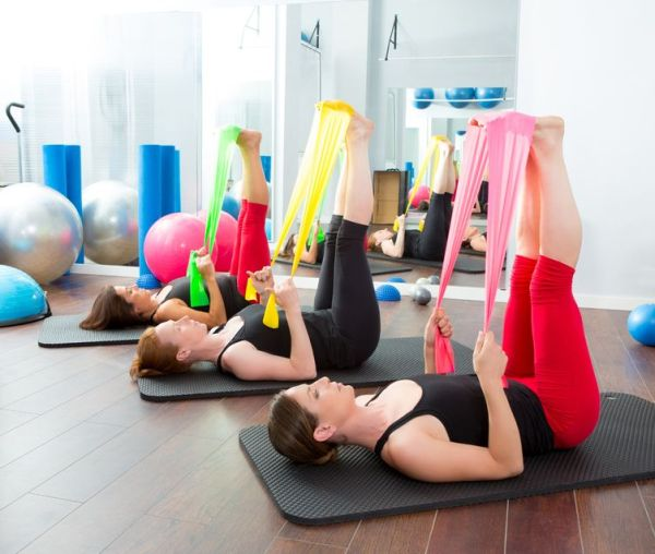 15444290 - aerobics pilates women group with rubber bands in a row at fitness gym
