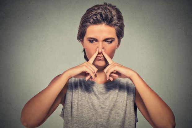 45694376 - headshot woman pinches nose with fingers hand looks with disgust away something stinks bad smell situation isolated on gray wall background. human face expression body language reaction