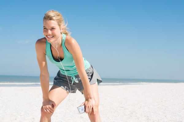 54852461 - young happy athlete tired after exercising. woman resting at beach and listening to music after a routine workout. young woman enjoying music at beach after run.