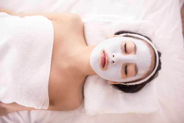 38287265 - spa therapy for young asian woman receiving facial mask at beauty salon.
