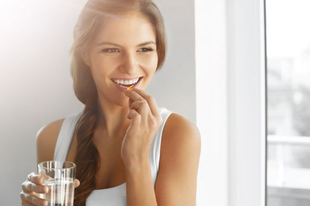 47895081 - diet. nutrition. vitamins. healthy eating, lifestyle. close up of happy smiling woman taking pill with cod liver oil omega-3 and holding a glass of fresh water in morning. vitamin d, e, a fish oil capsules.