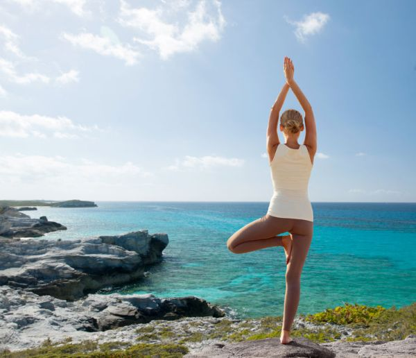 34814661 - fitness, sport, people and lifestyle concept - young woman making yoga exercises on beach from back