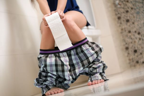 53597179 - woman with stomach problems on toilet