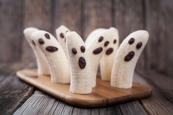 47213557 - homemade halloween scary banana ghosts monsters with chocolate faces. healthy natural vegetarian snack recipe for party decoration on vintage wooden table background.