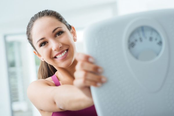 43396935 - happy young woman losing weight and showing a scale, dieting and fitness concept