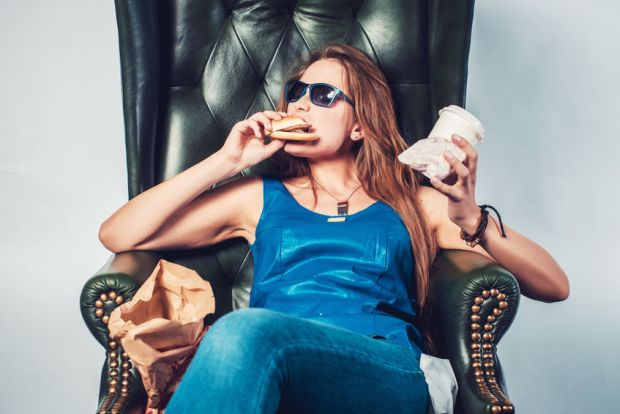 43880735 - funny crazy woman eating hamburger junk food and fries sitting in chair