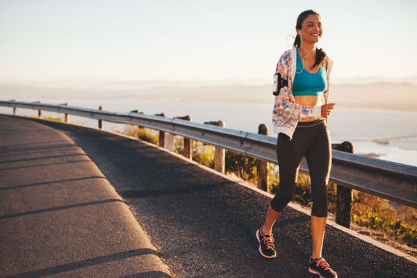 42096367 - portrait of happy young woman running on country road. caucasian female model on morning run outdoors.