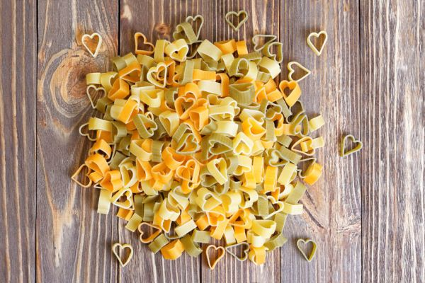 50919467 - durum wheat heart-shaped pasta with vegetables on wooden background for valentine day. top view.