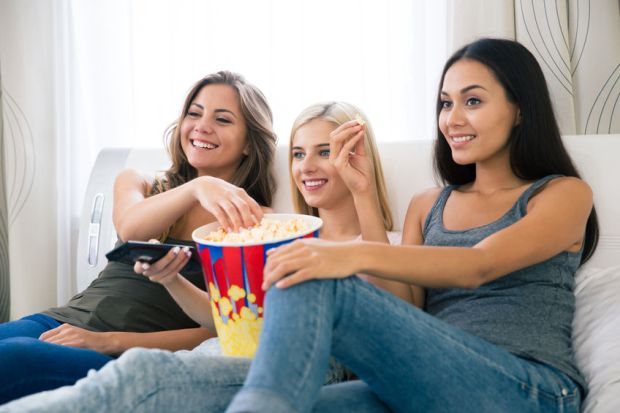 46468406 - portrait of a three happy girlfriends eating popcorn and watching tv at home