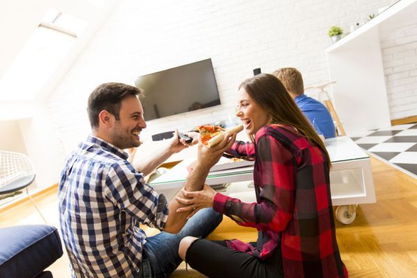 57375748 - couple eating pizza and a man holding tv remote control