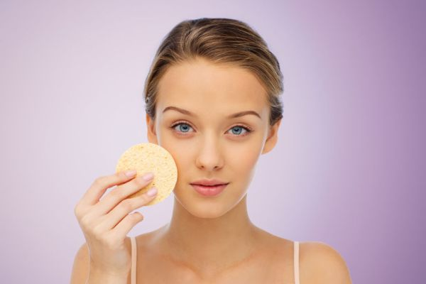 51237327 - beauty, people and skincare concept - young woman cleaning face with exfoliating sponge over violet background