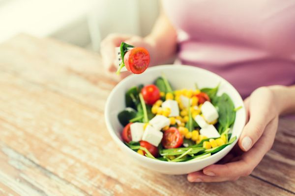 58800303 - healthy eating, dieting and people concept - close up of young woman eating vegetable salad at home