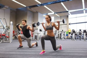 35196148 - sport, bodybuilding, lifestyle and people concept - young man and woman with barbell flexing muscles and making shoulder press lunge in gym