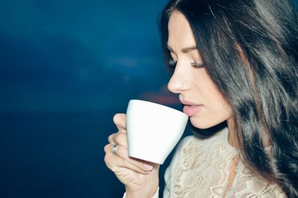57162512 - closeup of beautiful woman smiling and holding coffee cup at night outdoors