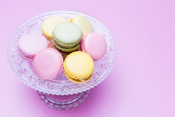 41535871 - macaroons in a glass bowl on violet background