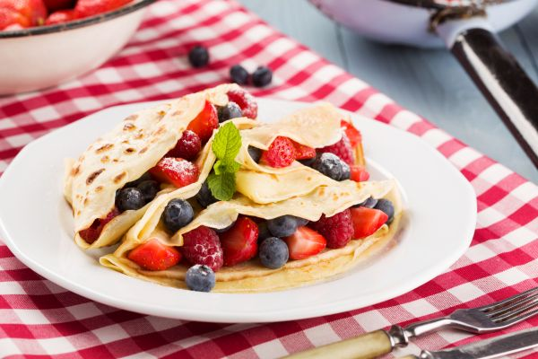 Delicious pancakes with raspberries, blueberries and strawberries. Sprinkled with powdered sugar.