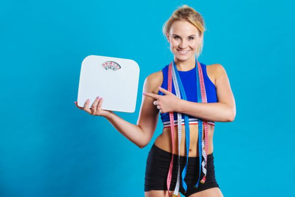 62378760 - healthy lifestyle. fitness woman with many measure tapes holding weight scale studio shot blue background