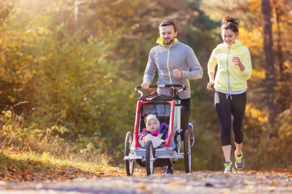 50204808 - beautiful young family with baby in jogging stroller running outside in autumn nature