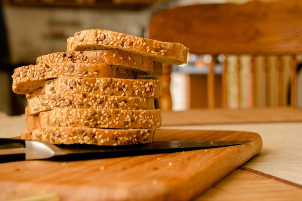 56078783 - fresh whole wheat bread slices on a wooden