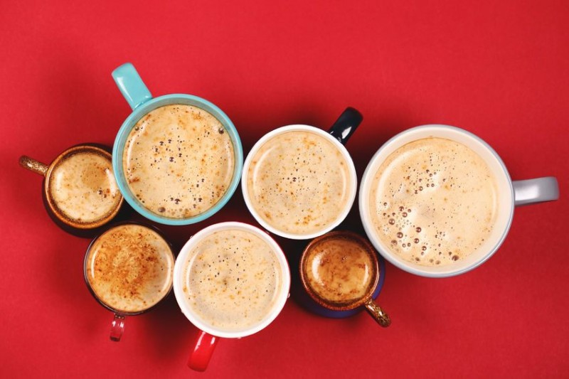 49386974 - many different cups of coffee and cappuccino on red background