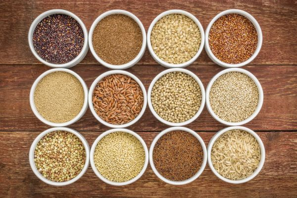 38204791 - healthy, gluten free grains collection (quinoa, brown rice, millet, amaranth, teff, buckwheat, sorghum) , top view of small round bowls against rustic wood
