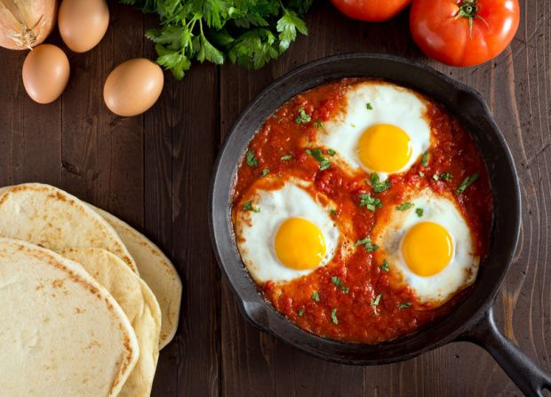 38562163 - shakshuka with eggs, tomato, and parsley in a cast iron pan.