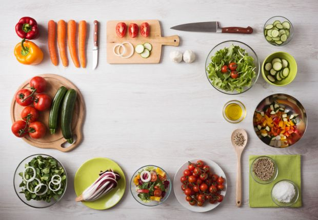39363721 - healthy eating concept with fresh vegetables and salad bowls on kitchen wooden worktop, copy space at center, top view