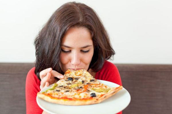15616794 - closeup portrait of a young woman eating a pizza on a plate